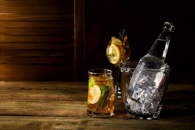 Uísque com base cocktail com balde de gelo de vidro no backgorund de madeira escura Foto Premium