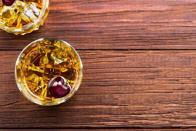 Uísque com gelo e cereja em dois copos Foto Premium