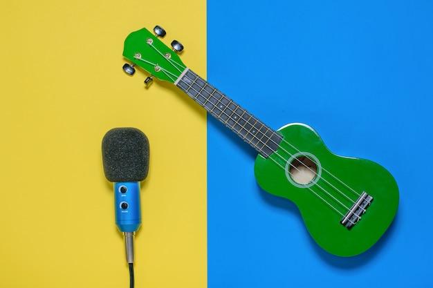 Ukulele e microfone com fios em azul e luz de fundo amarelo. a vista do topo. Foto Premium