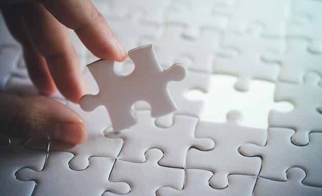 Última peça de jigsaw branco simples, segurando com a mão, passo do conceito de sucesso Foto Premium