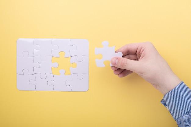 Última peça de quebra-cabeça na mão quebra-cabeça branca Foto Premium