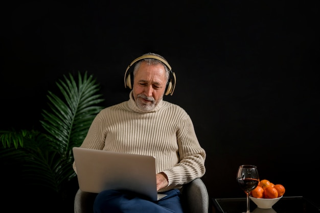 Último homem assistindo filme perto de tangerinas e vinho Foto gratuita