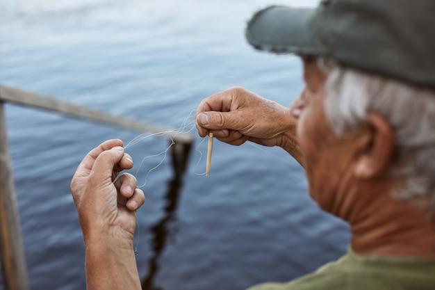 Último homem com cabelos grisalhos, vestindo boné de beisebol e camiseta verde iscas vara de pesca, macho idoso, passar um tempo perto do rio ou lago, tendo o resto ao ar livre. Foto gratuita