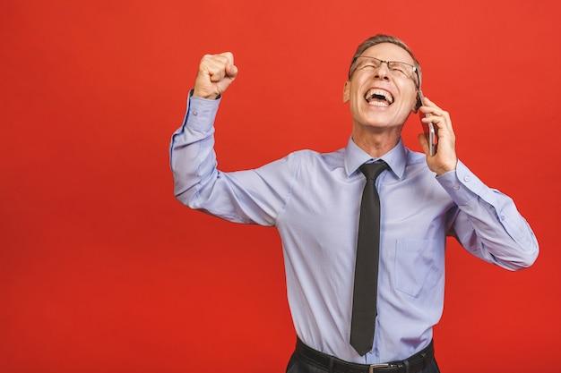 Último homem comemorando louco e espantado com sucesso com os braços levantados e os olhos abertos, gritando animado. conceito vencedor. usando o telefone Foto Premium