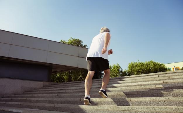 Último homem como corredor com braçadeira ou rastreador de fitness nas ruas da cidade. modelo masculino caucasiano, praticando jogging e treinamentos cardio na manhã de verão. estilo de vida saudável, esporte, conceito de atividade. Foto gratuita