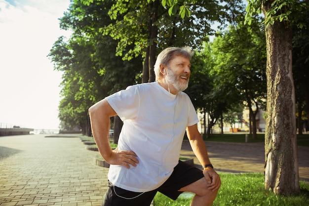Último homem como corredor na rua da cidade. modelo masculino caucasiano, corrida e treinamento cardiovascular na manhã de verão. fazendo exercícios de alongamento perto do prado. estilo de vida saudável, esporte, conceito de atividade. Foto gratuita
