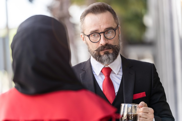 Último homem em um terno de negócio inteligente, falando com as pessoas e sentado na mesa de centro ao ar livre. Foto Premium