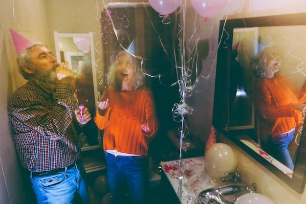 Último homem soprando o chifre de festa e mulher jogando confete no ar no aniversário Foto gratuita