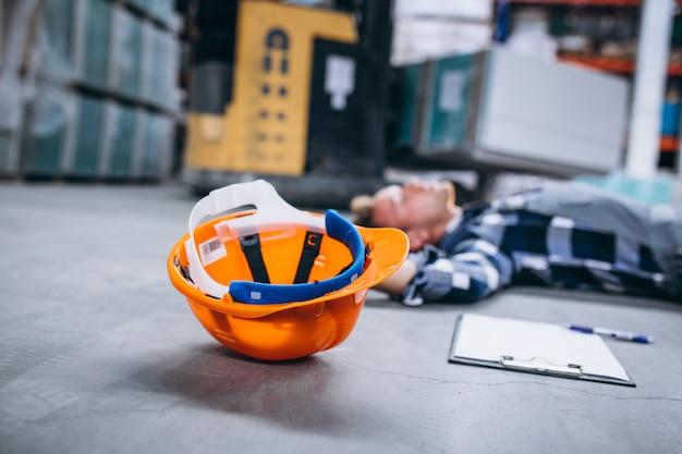 Um acidente em um armazém, homem no chão Foto gratuita