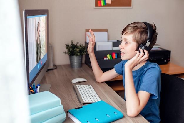 Um adolescente se comunica com parentes por meio de uma videoconferência com câmera da web no computador em casa. Foto Premium