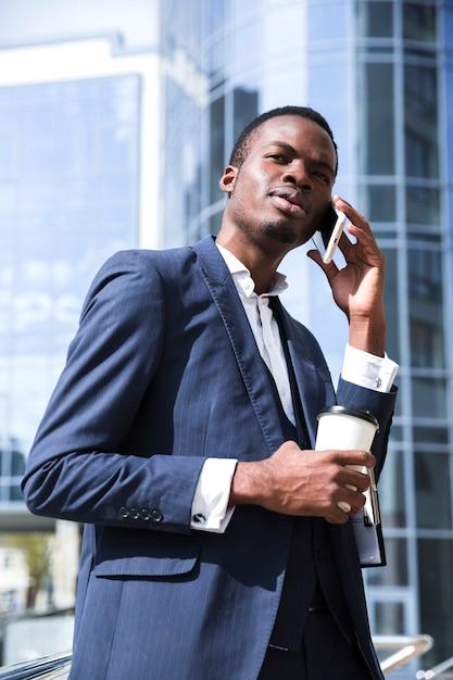 Um, africano, homem negócios, falando telefone móvel, segurando, copo café descartável Foto gratuita