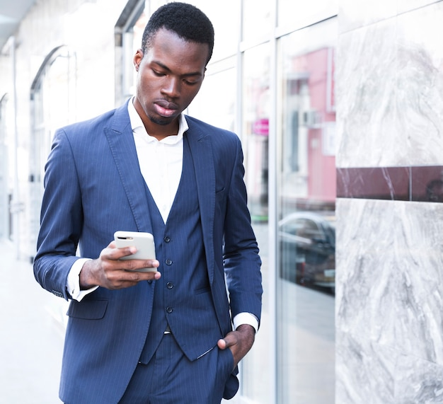 Um, africano, jovem, homem negócios, com, seu, mãos, em, seu, bolso, usando, telefone móvel Foto gratuita