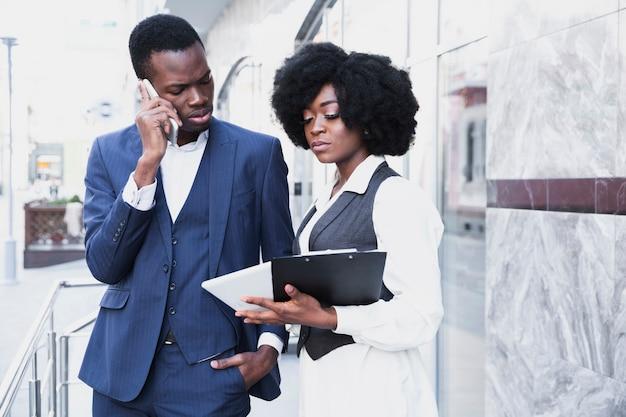 Um, africano, jovem, homem negócios, falando telefone móvel, olhar, tablete digital, segure, por, seu, colega Foto gratuita