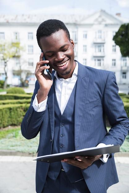 Um, africano, jovem, homem negócios, olhar, prancheta, falando telefone móvel Foto gratuita
