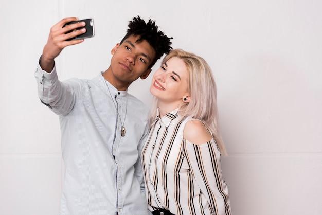 Um, africano, menino adolescente, levando, selfie, com, dela, namorada, ligado, telefone móvel Foto gratuita