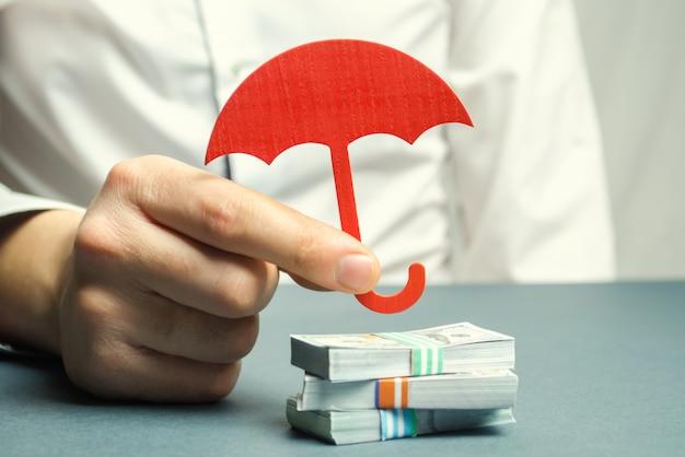 Um agente de seguros detém um guarda-chuva vermelho Foto Premium