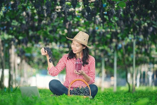 Um agricultor de uva desfrutar suco de uva espremido na hora Foto gratuita