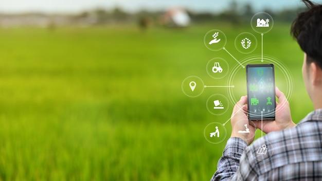 Um agricultor está trabalhando no campo usando um telefone celular com a tecnologia innovation para um sistema agrícola inteligente. Foto Premium