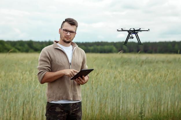 Um agricultor gerencia um drone sobre terras agrícolas. Foto Premium