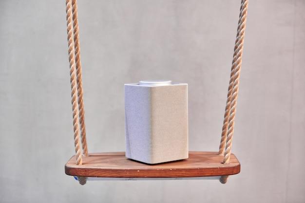 Um alto-falante bluetooth cinza, quadrado, coluna de música fica em um azulejo de quadrados brancos Foto Premium