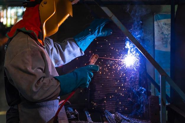 Um artesão está soldando com aço da peça. pessoa que trabalha sobre aço de soldador. Foto Premium