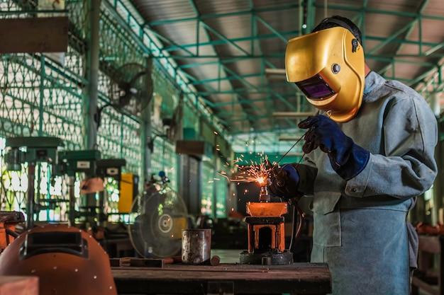 Um artesão está soldando com aço de peça de trabalho. Foto Premium