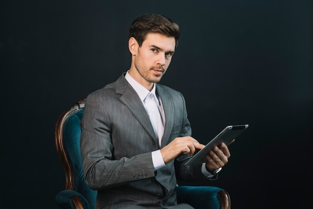 Um, atraente, jovem, homem negócios, sentando, em, poltrona, usando, tablete digital Foto gratuita