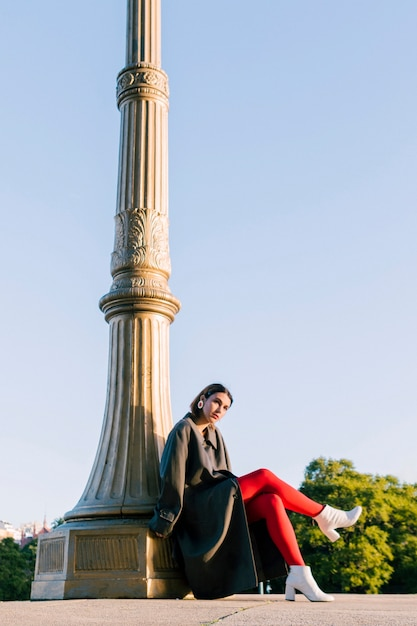 Um, atraente, mulher jovem, sentando, sob, a, pilar, com, dela, cruzado, pernas Foto gratuita