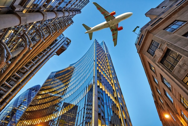 Um avião a jato voando sobre a cidade Foto Premium
