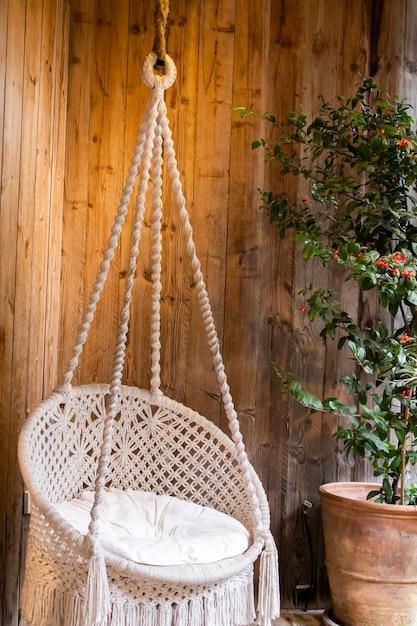 Um balanço branco feito de corda trançada com belos padrões e acolchoado com almofadas brancas Foto Premium