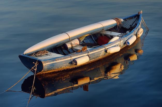 Um barco de madeira velho com um caiaque que encontra-se nele na água do lago garda. Foto Premium
