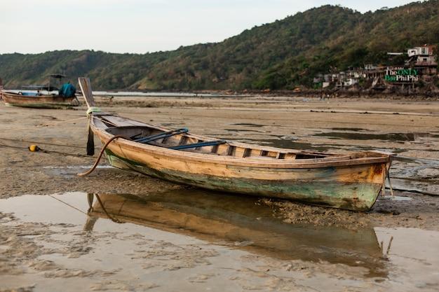 Um barco de pesca de madeira estava no fundo arenoso do oceano na maré baixa. Foto Premium