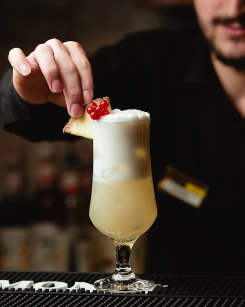 Um barman que decora o suco de abacaxi com bagas e fatia de abacaxi. Foto gratuita