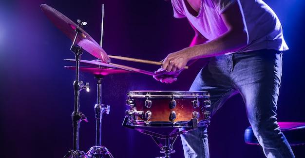 Um baterista toca bateria em uma parede azul Foto gratuita