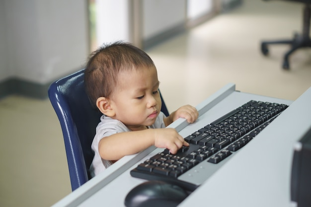Um bebê asiático tentando usar o computador desktop Foto Premium