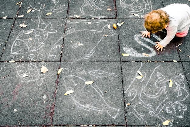 Um bebê de 1 ano joga sentado no chão de um parque com giz para desenhar no chão preto. Foto Premium
