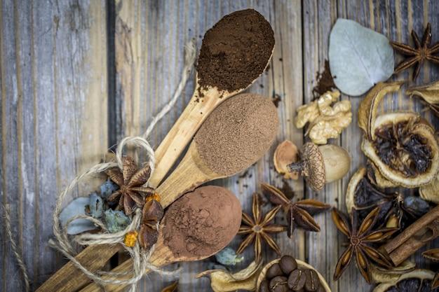Um belo arranjo de limões secos, canela, café em colheres de madeira na madeira Foto gratuita