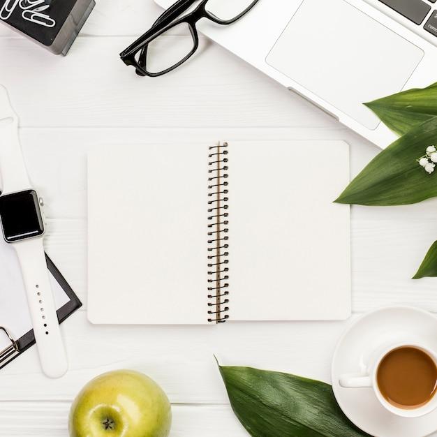 Um bloco de notas em espiral aberto rodeado de artigos de papelaria, maçã e relógio inteligente na mesa de escritório Foto gratuita