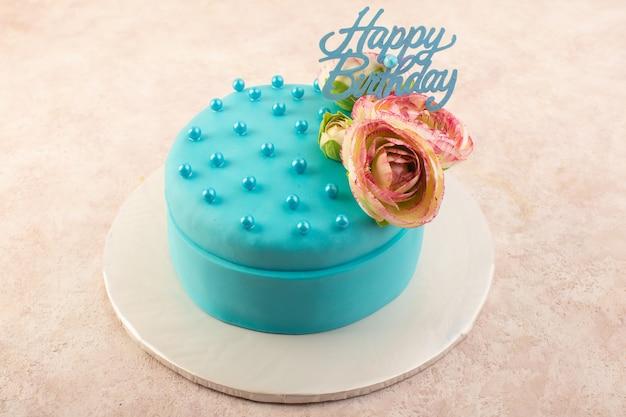 Um bolo de aniversário azul com uma flor no topo da mesa rosa Foto gratuita