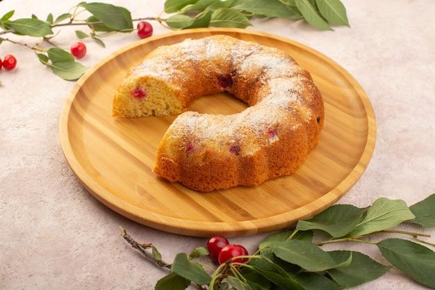 Um bolo de cereja frontal na mesa de madeira com cerejas frescas na mesa rosa Foto gratuita