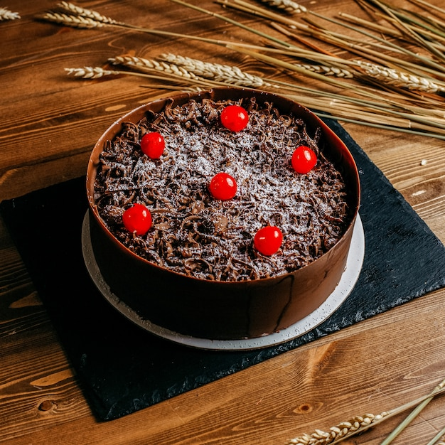 Um bolo de chocolate de vista frontal decorado com cerejas redondo delicioso dentro de marrom bolo pan aniversário doce confeitaria no fundo marrom Foto gratuita