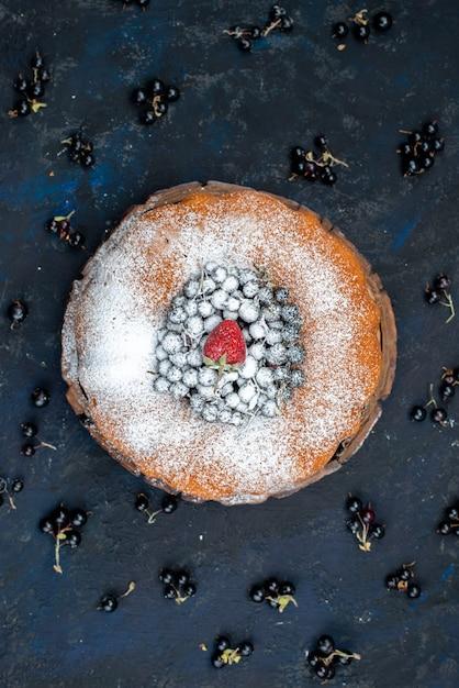 Um bolo de frutas delicioso e redondo formado com azul fresco, bagas no escuro, biscoito doce com açúcar Foto gratuita