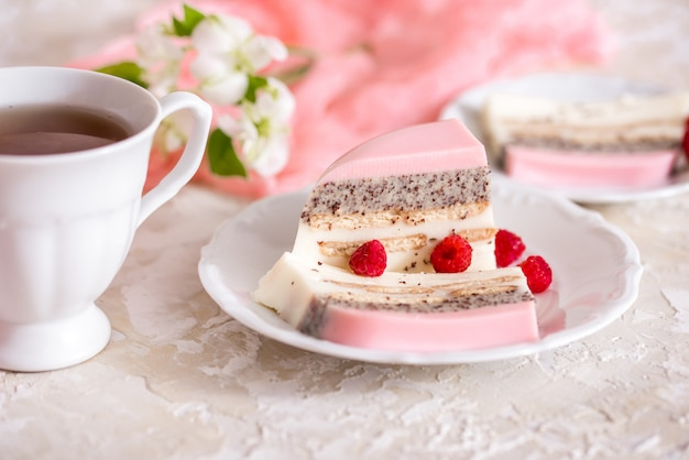 Um bolo doce rosa copo rosa com bule de chá e copo em cima da mesa Foto Premium