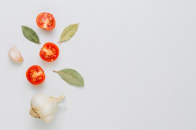 Um bulbo de alho orgânico inteiro e cravo com folhas de louro e tomates cereja cortados ao meio em pano de fundo branco Foto gratuita