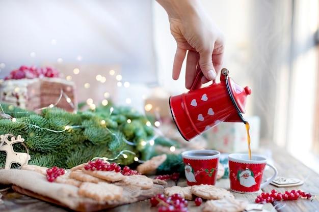 Um bule de café em suas mãos derrama café, frutas e biscoitos, presentes, perto de uma árvore de natal em uma mesa de madeira perto da janela Foto Premium