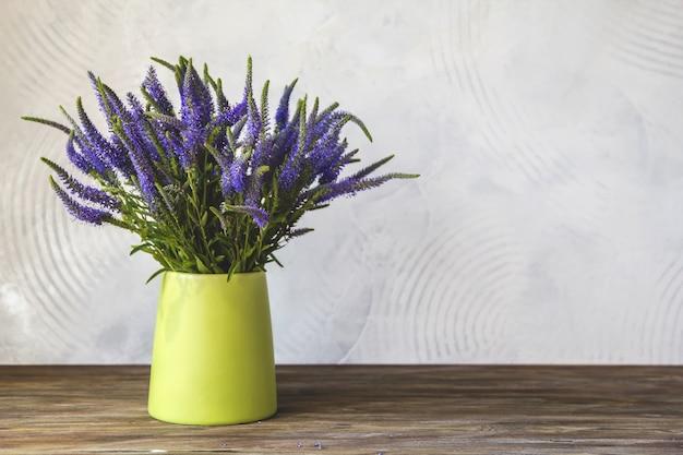 Um buquê de flores azuis de verônica em um vaso verde Foto Premium