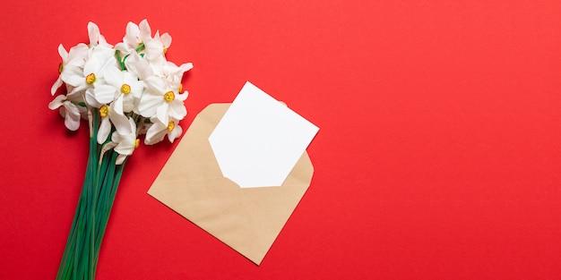 Um buquê de flores brilhantes com elaboração de conversor e uma folha em branco de papel maquete Foto Premium