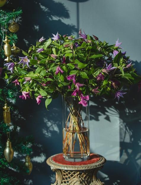 Um buquê de flores violetas com folhas verdes dentro de um vaso Foto gratuita