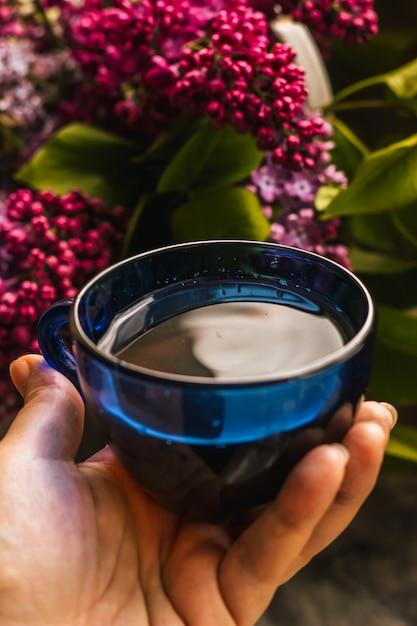 Um buquê de lilás rosa roxo lindo e uma xícara de chá quente Foto Premium