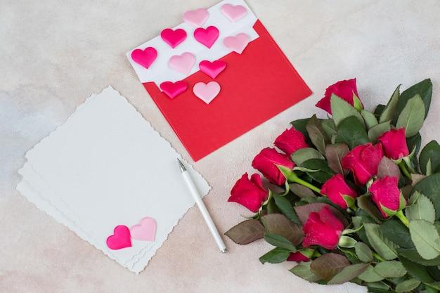 Um buquê de rosas vermelhas, corações de cetim, folhas de papel, uma caneta e um envelope vermelho Foto Premium
